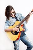 Fashion portrait of a teenager playing guitar in studio wearing sunglasses and jeans jacket Stock Photos