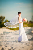 Fashion portrait of tender stylish bride with simple modern wedd. Ing dress posing with amazing exotic white lotus bouquet at the beach. Evening golden sunlight Royalty Free Stock Images