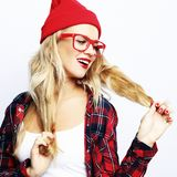 Portrait of trendy casual young woman wearing red glasses and hat, posing over white background. Hipster style.Close up. royalty free stock images