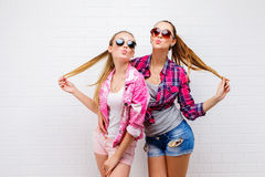 Fashion portrait of two friends posing. modern lifestyle.two stylish sexy hipster girls best friends ready for party.Two. Young girl friends standing together Stock Image