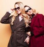 Fashion portrait of two girls, best friends posing indoor on beige background wearing winter stylish coat. Positive fashion portrait of two girls, best friends Royalty Free Stock Image