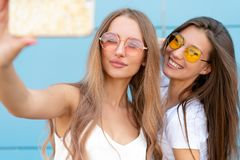 Fashion portrait of two pretty smiling hipsters woman in sunglasses holding smartphone and making selfie against the. Fashion portrait of two pretty smiling stock image