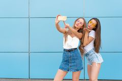 Fashion portrait of two pretty smiling hipsters woman in sunglasses holding smartphone and making selfie against the. Fashion portrait of two pretty smiling stock photos