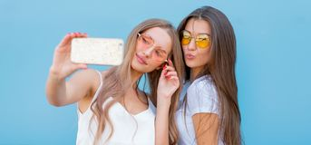 Fashion portrait of two pretty smiling hipsters woman in sunglasses holding smartphone and making selfie against the. Fashion portrait of two pretty smiling royalty free stock images