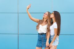 Fashion portrait of two pretty smiling hipsters woman in sunglasses holding smartphone and making selfie against the. Fashion portrait of two pretty smiling stock photography