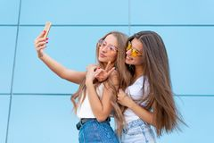 Fashion portrait of two pretty smiling hipsters woman in sunglasses holding smartphone and making selfie against the. Fashion portrait of two pretty smiling royalty free stock image