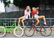 Fashion portrait of two woman on a bicycles in a summertime Stock Image