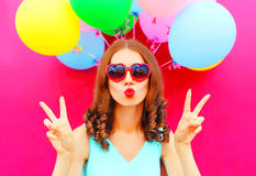 Fashion portrait woman blowing lips holds an air colorful balloons on pink background Royalty Free Stock Photography