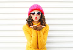 Fashion portrait woman blowing red lips makes sends air kiss. Wearing colorful knitted hat over white background Stock Photos