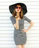 Fashion portrait woman blowing red lips sending sweet air kiss in black summer straw hat on white wall. Background stock photos