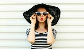 Fashion portrait woman blowing red lips sending sweet air kiss in black summer straw hat on white wall. Background royalty free stock images