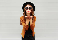 Fashion portrait woman blowing red lips sends air sweet kiss wearing black hat, sunglasses, jacket over urban grey Stock Photos