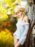 Fashion portrait woman with hat and white shirt in the autumn day. Very cute blond woman outdoor with a hat in a autumn forest.Young sensual blonde girl royalty free stock photography