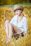 Fashion portrait woman with hat and white shirt sitting on a hay stack. Very cute blond woman sitting down outdoor on the yellow grass with a hat Royalty Free Stock Photos