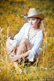 Fashion portrait woman with hat and white shirt sitting on a hay stack Stock Photography