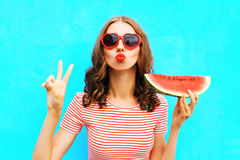 Fashion portrait woman is holding a slice of watermelon and blowing lips Stock Photos