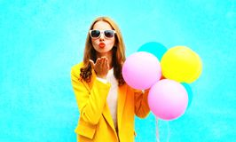 Fashion portrait woman holds balloons sends an air kiss in yellow Stock Images