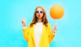 Fashion portrait woman holds orange air balloon in yellow coat Royalty Free Stock Photo