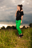 Fashion portrait of a woman with interesting hairdo posing outdoors. Young brunette woman with interesting hairdo posing outside, wearing bright green pants Royalty Free Stock Images