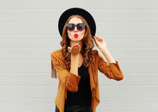 Fashion portrait woman model blowing red lips sends air sweet kiss wearing black hat, sunglasses over urban grey Stock Image