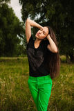 Fashion portrait of a woman with natural long hair posing outdoors. Young brunette woman with long natural hair posing outside, wearing bright green pants Royalty Free Stock Image