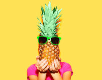 Fashion portrait woman and pineapple with sunglasses over colorful yellow. Background Royalty Free Stock Photos