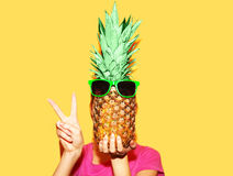 Fashion portrait woman and pineapple with sunglasses over yellow Royalty Free Stock Image