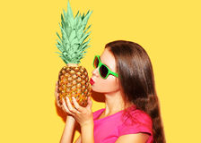 Fashion portrait woman and pineapple with sunglasses over yellow background Royalty Free Stock Photo