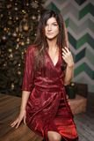 Fashion portrait of woman in red dress posing on camera on Christmas tree background royalty free stock photography