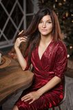 Fashion portrait of woman in red dress posing on camera on Christmas tree background stock photography