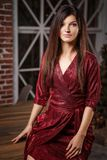 Fashion portrait of woman in red dress posing on camera on Christmas tree background royalty free stock photo