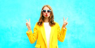 Fashion portrait woman sends an air kiss in a yellow coat posing Royalty Free Stock Image