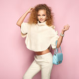Fashion portrait of woman in summer outfit. Girl posing on pink background. Blue handbag. Stylish curly hairstyle. Glamour lady Stock Photos
