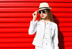 Fashion portrait woman in sunglasses and hat over red Stock Image