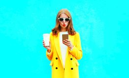 Fashion portrait woman is using smartphone holds cup of coffee Stock Image