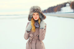 Fashion portrait woman wearing a coat jacket and hat over snow in winter Royalty Free Stock Photos