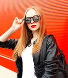 Fashion portrait woman wearing rock black jacket and sunglasses over red Stock Images
