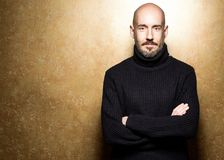 Fashion Portrait of 40-year-old man standing over light gold background in a black sweater. Close up. Classic style. Bald shaved. Head. Copy-space. Studio shot stock photos