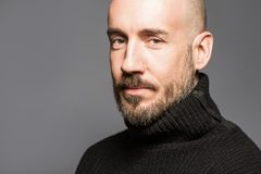 Fashion Portrait of a 40-year-old man standing over a light gray background in a black sweater. Close up. Classic style. Bald shav. Ed head. Copy-space. Studio Royalty Free Stock Photos