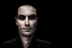 Fashion portrait of young adult vampire. Fashion portrait of young adult man vampire on black background Stock Photography