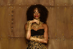 Fashion portrait of young african or black american model wearing gold clothes and makeup, bronze wall background Stock Images