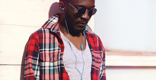 Fashion portrait young african man listens to music in headphones Stock Photo