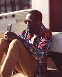 Fashion portrait young african man listens to music using smartphone royalty free stock photos