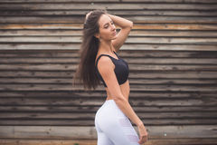 Fashion portrait of a young athletic fit girl in sportswear outdoors. Woman with perfect body Fitness concept. Royalty Free Stock Images