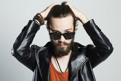 Fashion Portrait of young bearded man in leather jacket. Hipster in sunglasses Royalty Free Stock Images