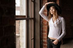 Fashion portrait of young beautiful confident woman wearing hat, posing in at the window royalty free stock photos
