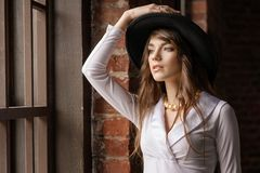 Fashion portrait of young beautiful confident woman wearing hat, posing in at the window royalty free stock images