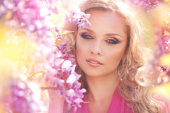 Fashion portrait of young beautiful girl posing against lilac bushes in blossom Royalty Free Stock Photography