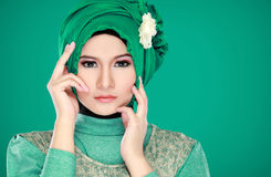 Fashion portrait of young beautiful muslim woman with green cost Stock Images