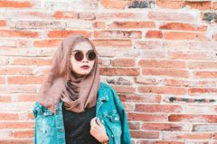 Fashion portrait of young beautiful muslim woman and old brick wall Royalty Free Stock Images